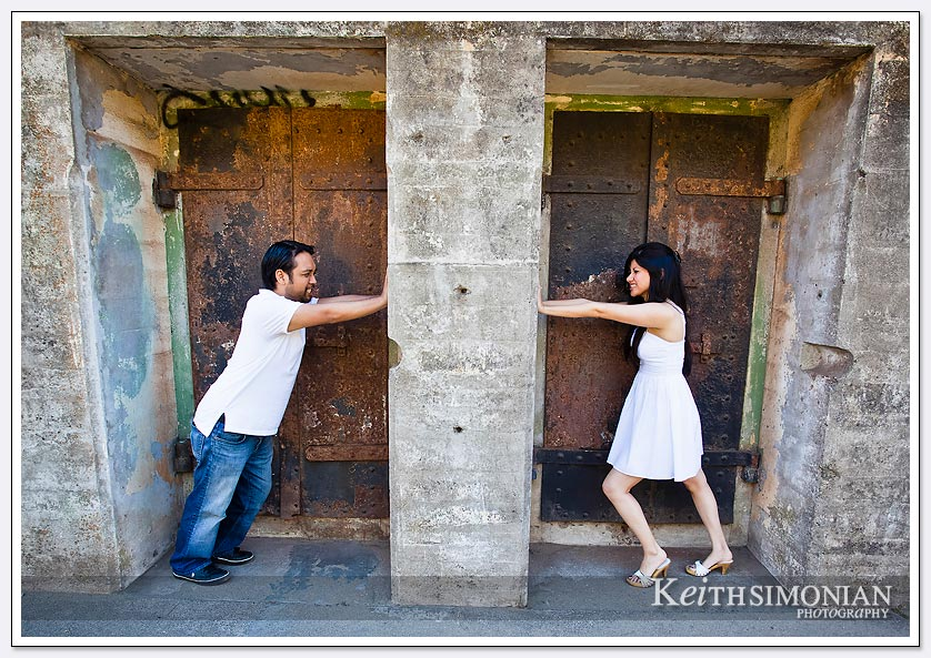 The couple tries to push the stone wall towards each other - San-Francisco-Engagement-Photos
