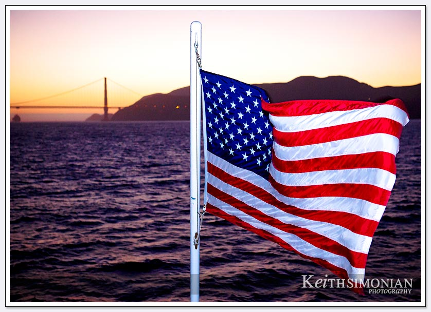 An American flags flies from the Commodore Cruise line with the Golden Gate Bridge as a backdrop