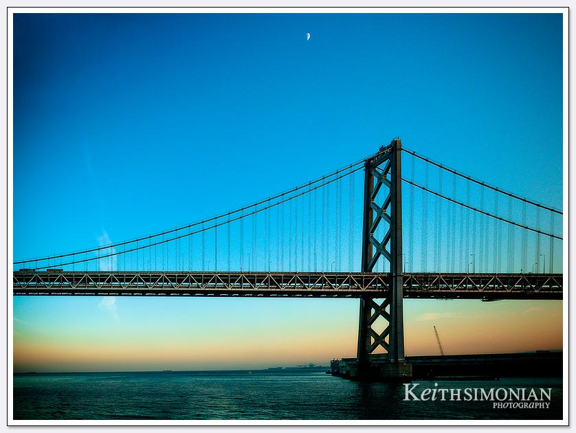 The moon rising over a sunset view of the Bay Bridge