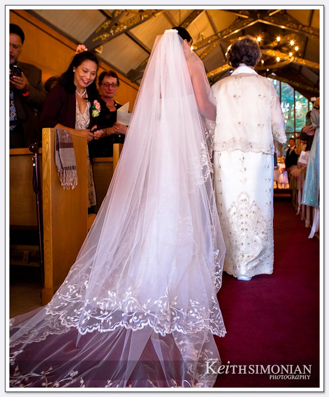 The bride walks up the aisle as her veil trails her