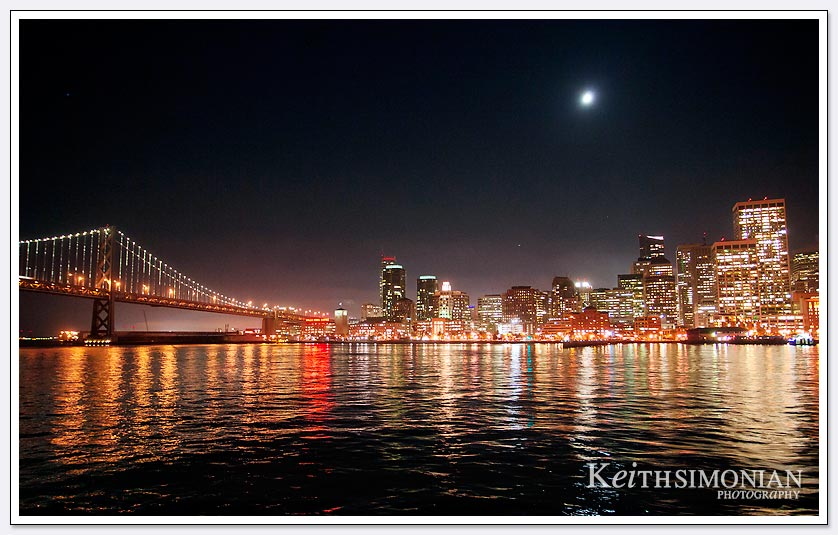 The moon sets over the San Francisco skyline and Bay Bridge