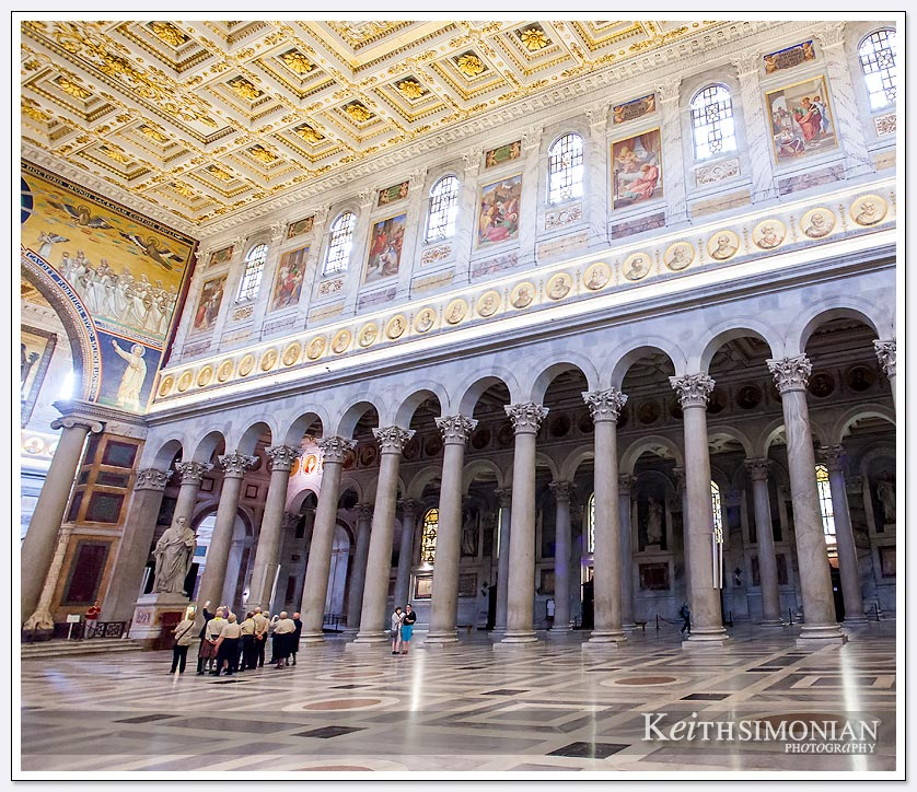 People in the photo give a sense of scale to the interior of Basilica Saint Paul Outside the Walls