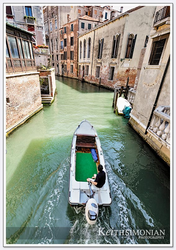 A boat passes under one of the many bridges that connect the islands of Venice, Italy.
