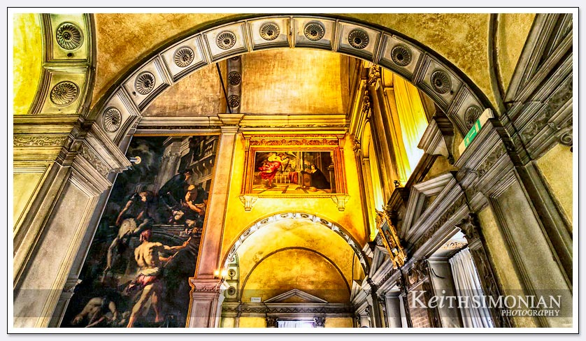 The yellow light shinning on the painting creates a dramatic canvas for the viewer in this Venice, Italy church.