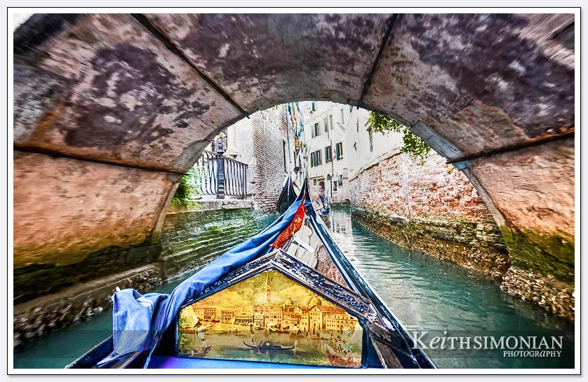 Gondola passes under one of the many bridges in Venice, Italy