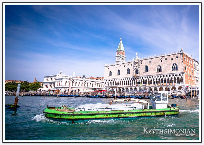 Green garbage boat in Venice Italy