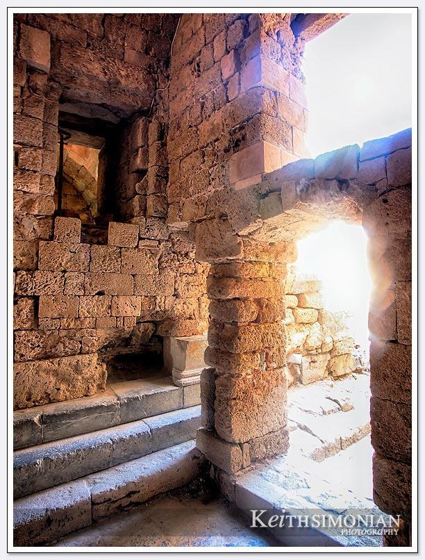 Sunlight steaming through the ancient ruins the make up the Acropolis of Lindos, Greece