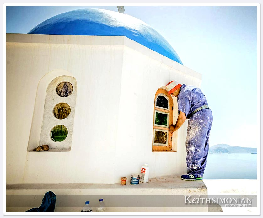 Worker painting some of the buildings white on Santorini, Greece