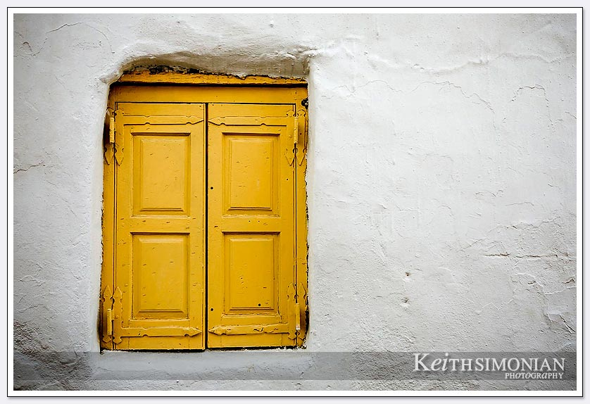 Yellow door and white building in the old town of Mykonos, Greece