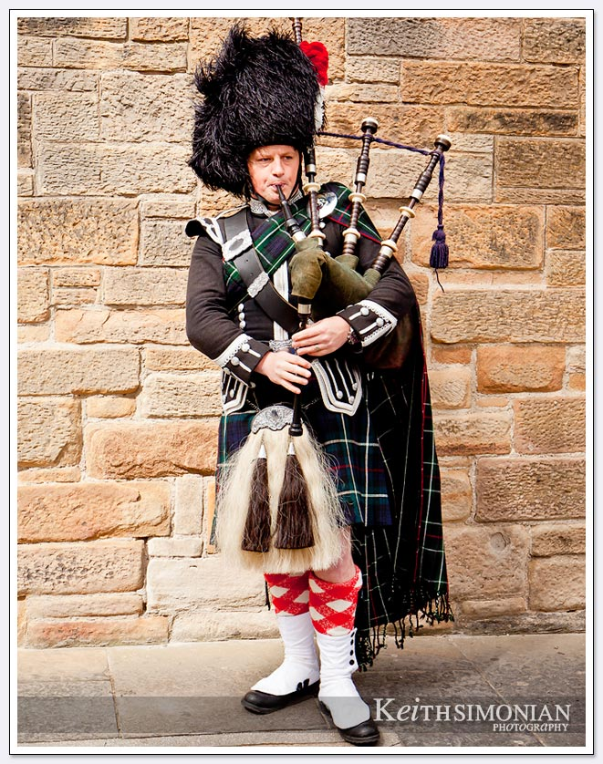 Man in kilt playing the bagpipes streets side in Edinburgh Scotland