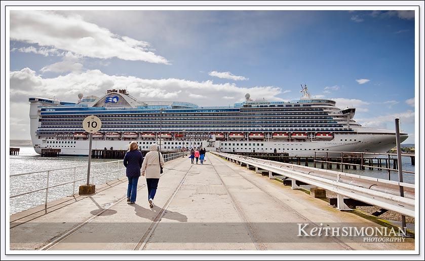 Passengers walk back to the Caribbean Princess docked in Invergordon Scotland