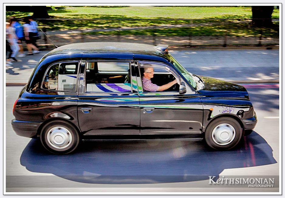 Distinctive black London cab zoom by