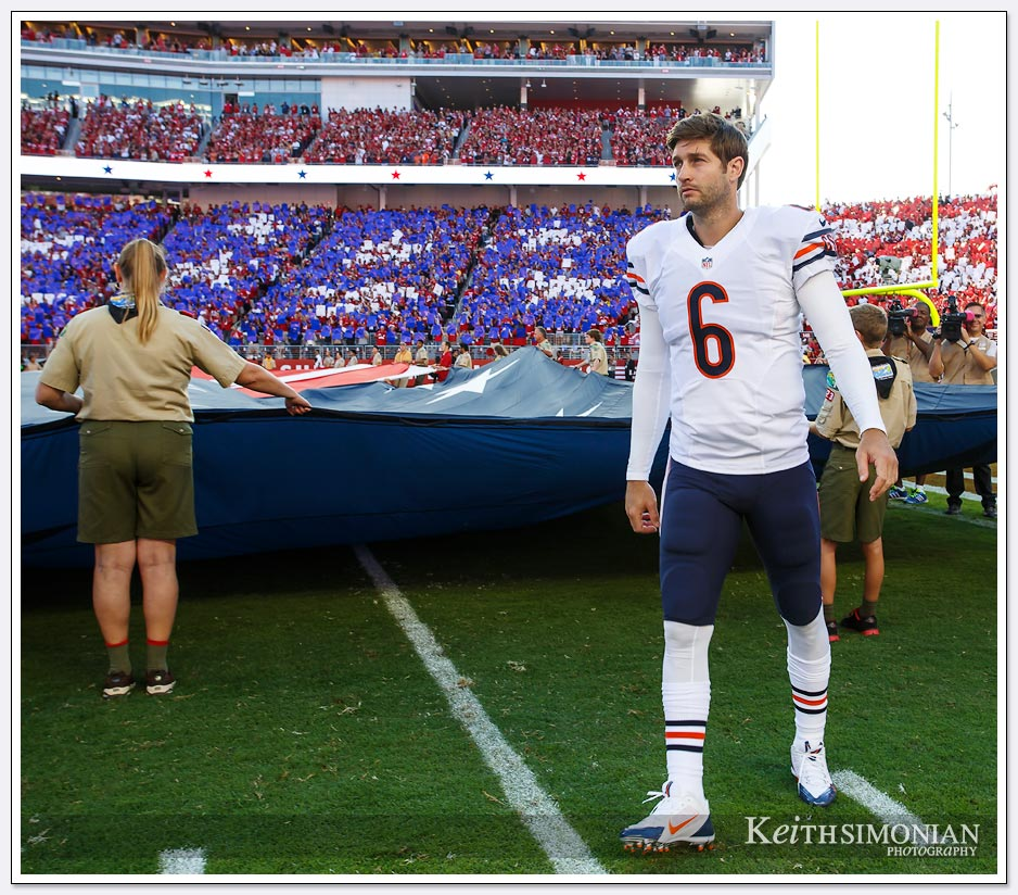 Chicago Bears quarterback Jay Cutler helps hold the American flag during the playing of the national anthem.