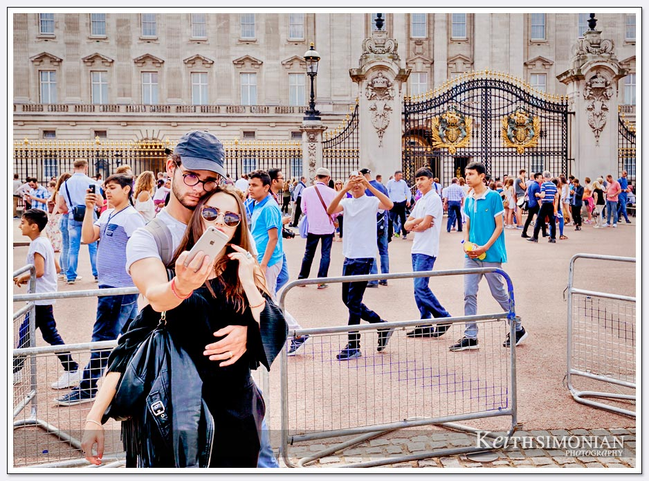 The many,many tourists taking photos outside Buckingham Palace in London England.
