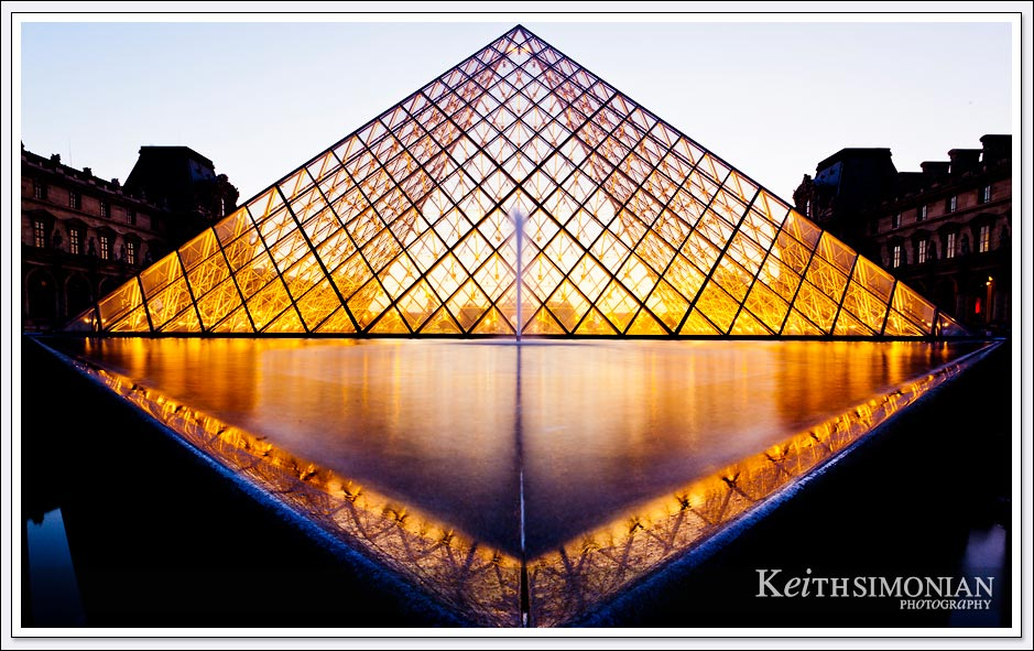 The reflection pond and the glass pyramid in the courtyard of the Louvre Museum at night - Paris France.