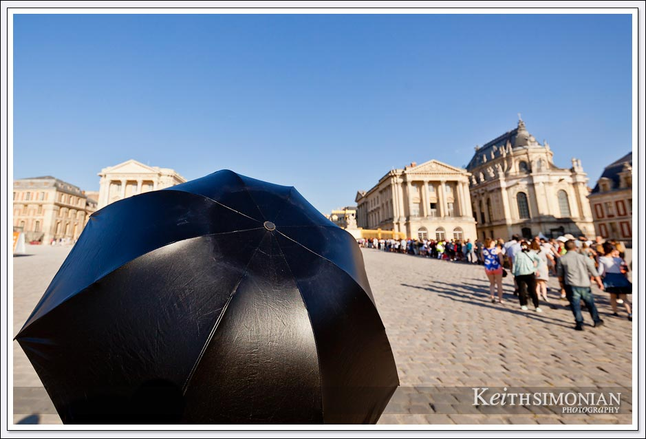 The line of visitors waiting to enter the Palace of Versailles can be quite long and this visitor took shade under a black umbrella.