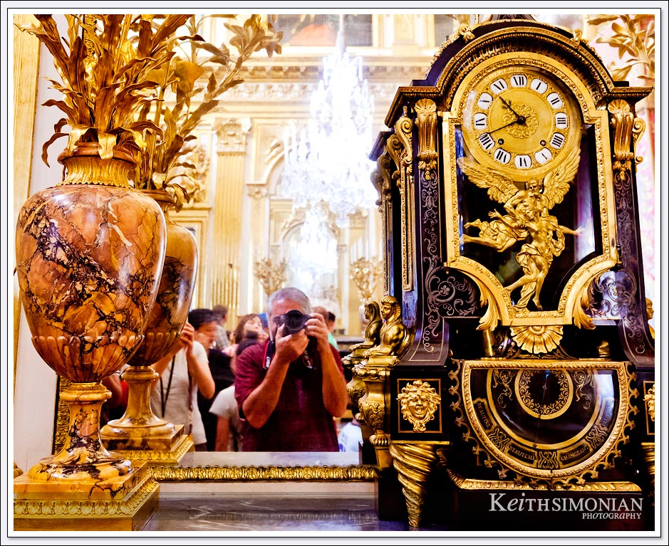 The palace of Versailles - elegant clock and vase with photographer's reflection in the mirror.