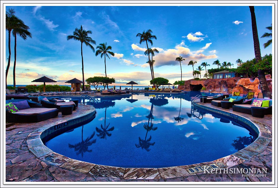 The clouds and palm trees reflect in the swimming pool of the Hyatt Regency Maui Resort and Spa in Maui Hawaii