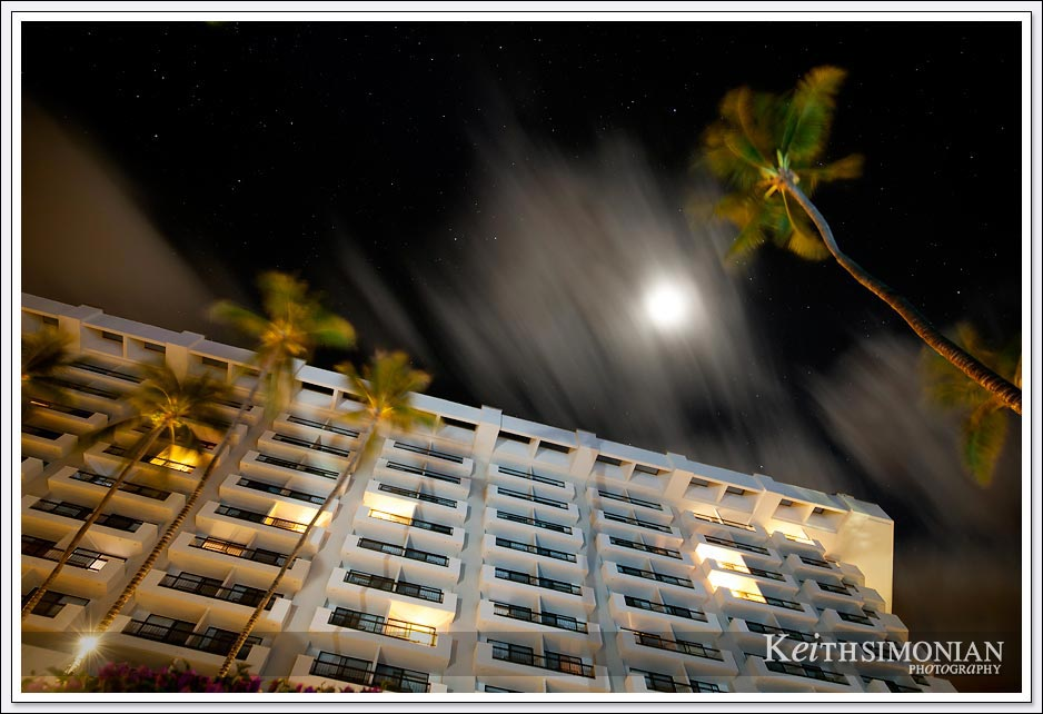A perfectly time cloud covers the moon during a long exposure photo of the Maui Resort Hotel - Maui Hawaii