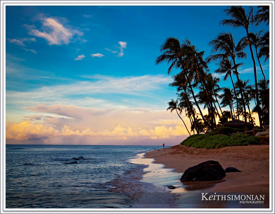 Sunrise along the Maui beach with a jogger running along the water line.