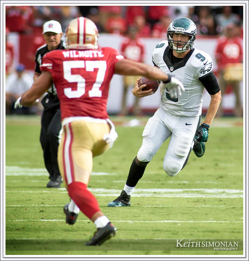Eagles quarterback Nick Foles scrambles down field as San Francisco 49er linebacker #57 Michael Wilhoite pursues him during this 2014 game at Levi's Stadium in Santa Clara, California
