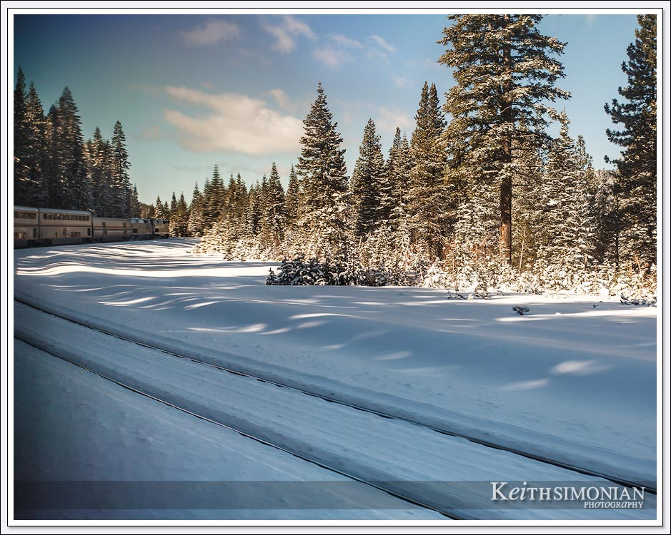 A bend in the tracks gives a view of the lead Amtrak cars passing through the snow.