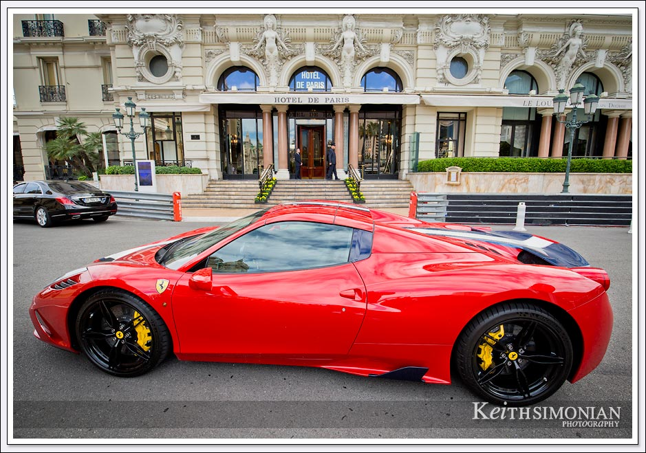 Red Ferrari parked in front of the Hotel de Paris in Monte Carlo.
