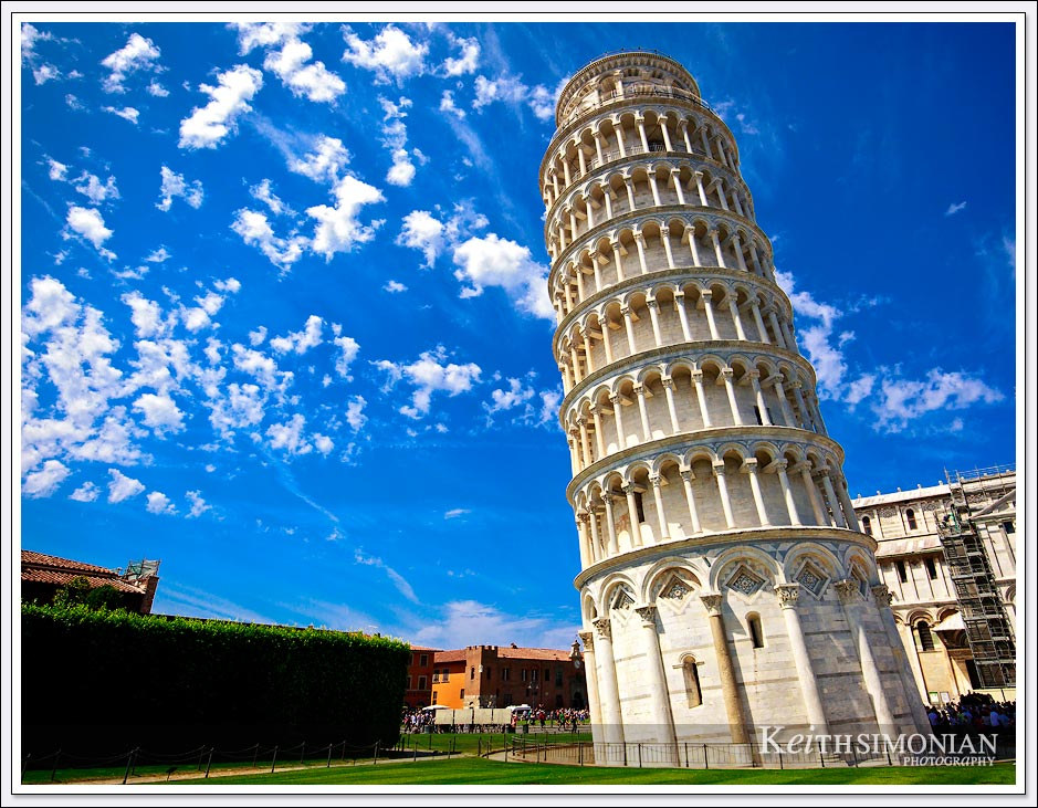 The leaning Tower of Pisa against a blue sky with puffy white clouds - Pisa, Italy