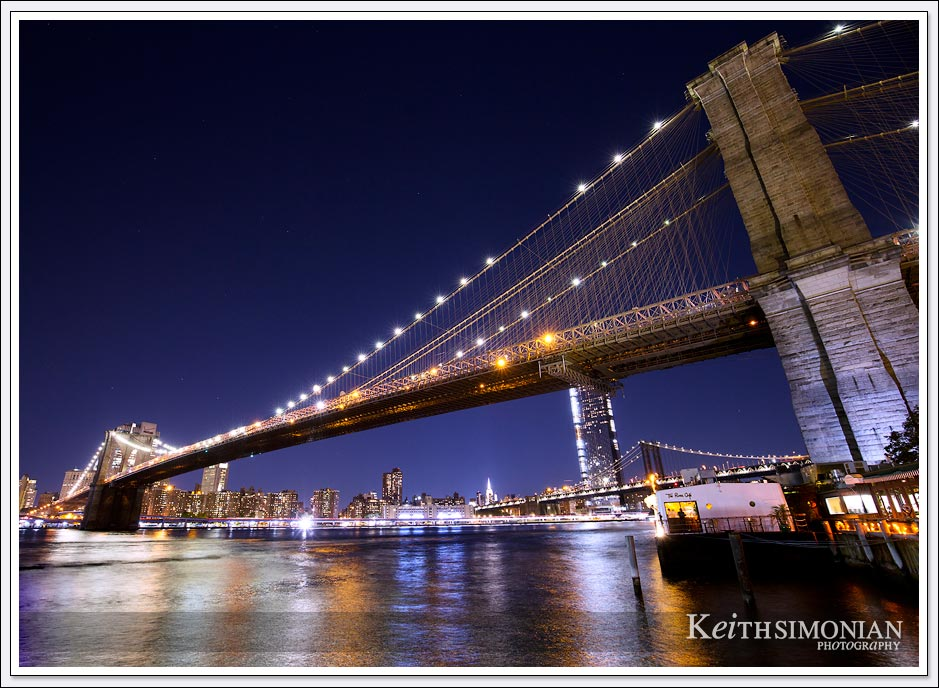 The night lights reflect off the East river as the Brooklyn bridge stands above.