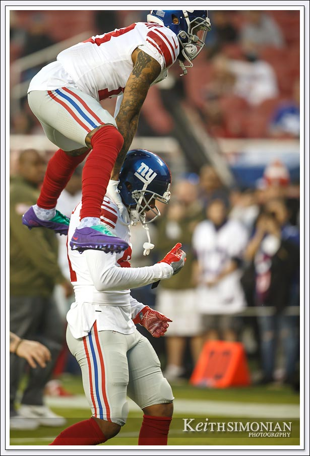 New York Giant Odell Beckham Jr. leaps over a player while leaving the field after pre game warm ups.