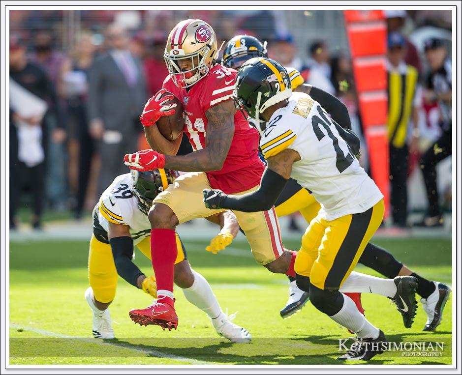 San Francisco 49er running back #31 Raheem Mostert tries to elude Pittsburgh Steeler defenders at Levi's Stadium in Santa Clara, CA