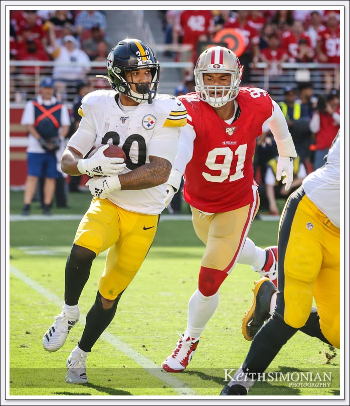 Pittsburgh Steeler running back #30 James Conner tries to elude San Francisco 49er defensive end #91 Arik Armstead at Levi's Stadium on September 22, 2019.