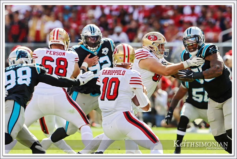 49ers quarterback Jimmy Garoppolo eludes several Carolina Panther rushers on this play.