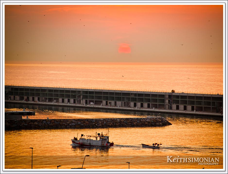 Fishing boat comes back to port during sunrise in Barcelona, Spain