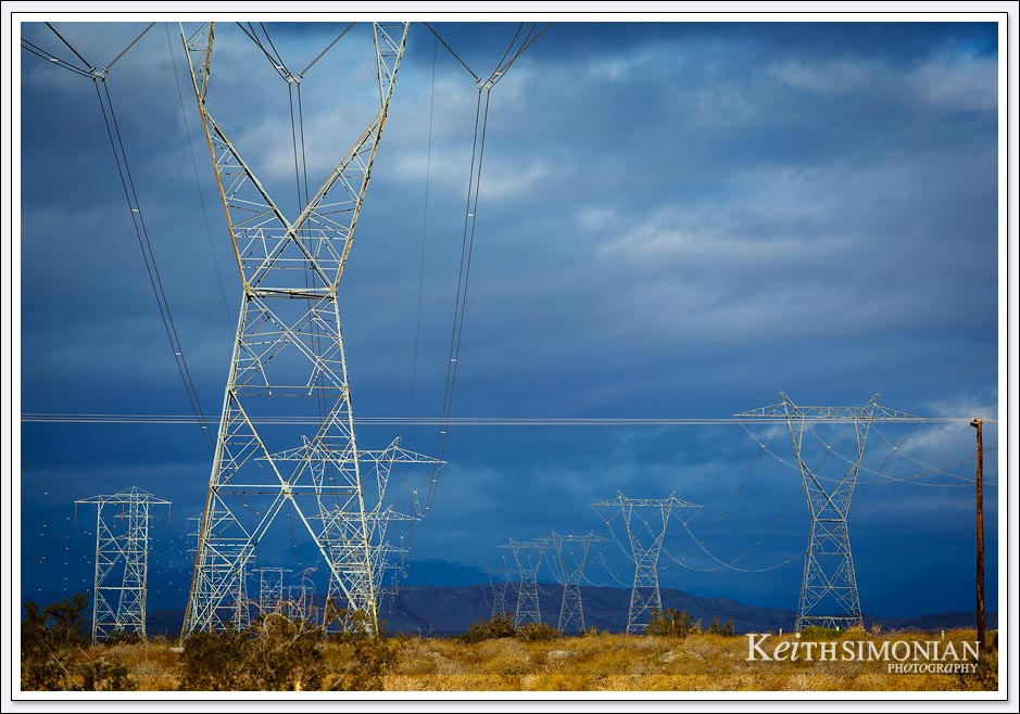 Dark clouds over electrical transmission lines in the California desert.