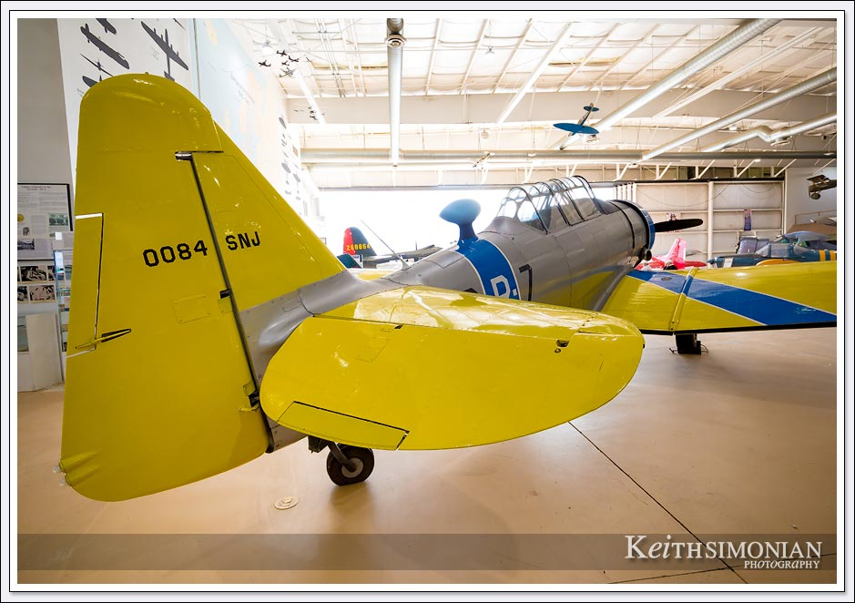 A yellow tailed North American AT-6/SNJ Texan sits in the Pacific hanger of the Palm Springs air museum.