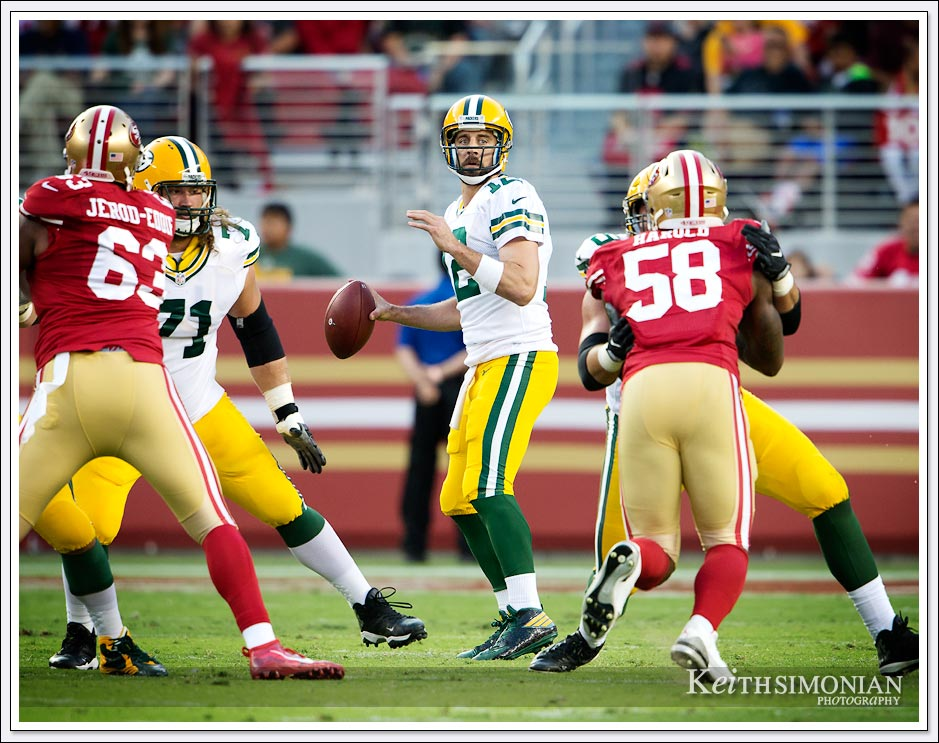 Green Bay Packer quarterback Aaron Rodgers looks for a receiver down field during a 2016 game against the San Francisco 49ers at Levi's stadium - Santa Clara, CA.