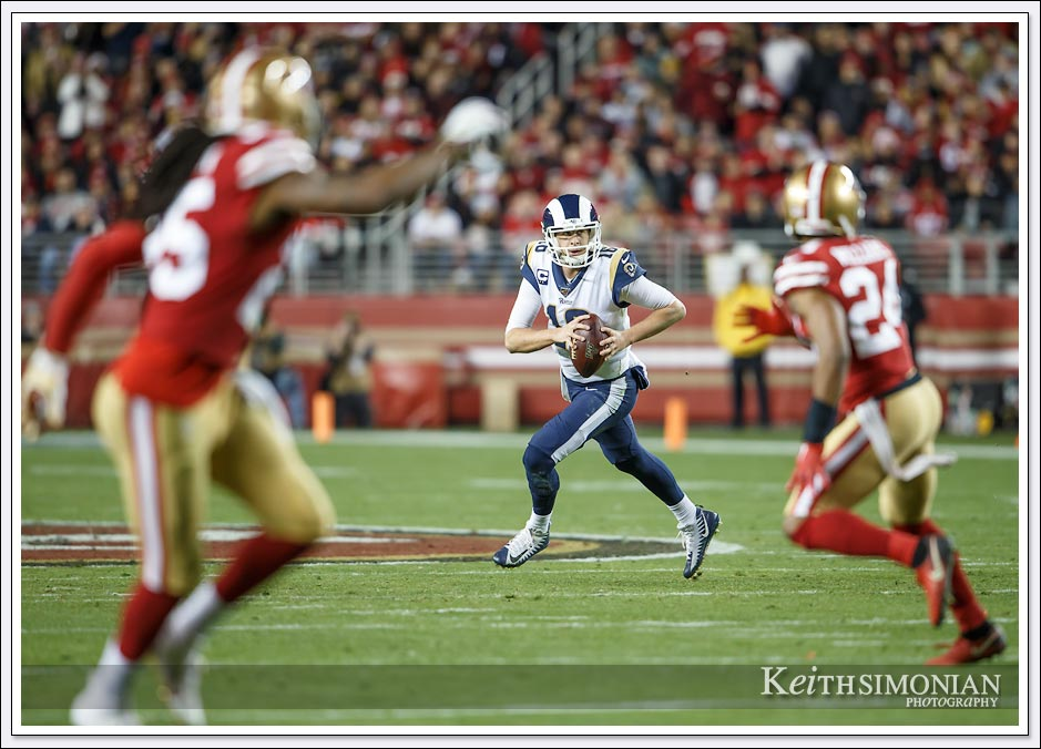 Los Angeles Ram quarterback #16 Jarad Goff rolls out to avoid a sack from the San Francisco 49ers defense.