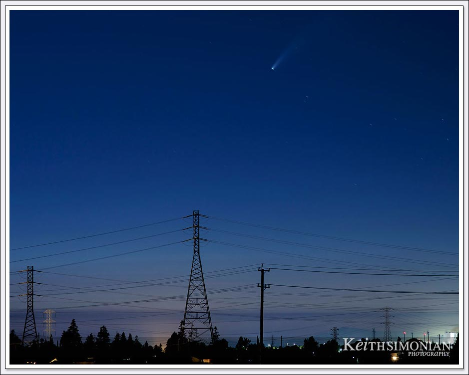 Comet NEOWISE streaks across the sky with power lines in the foreground.