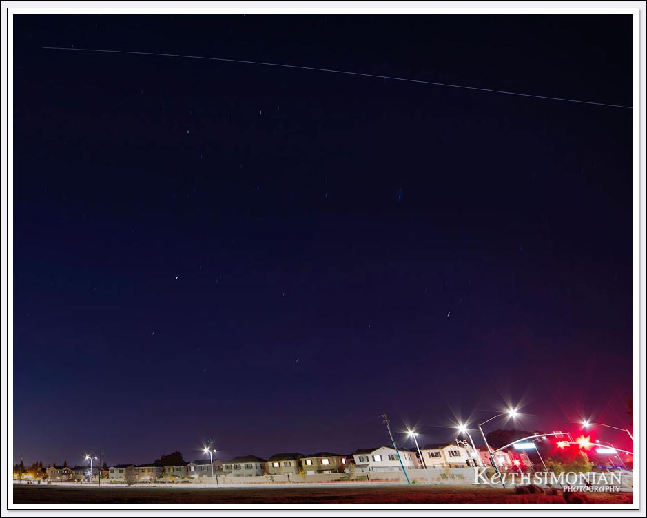 The International Space Station streaks across the night sky with city stop lights in the foreground.