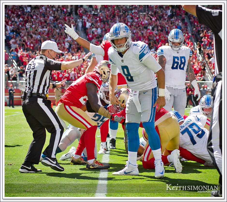 Detroit Lions quarterback #9 Matthew Stafford checks the sticks to see if the Lions got a first down.