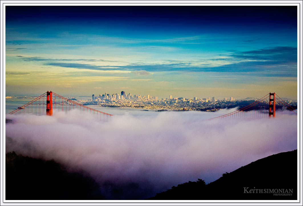 The Red Towers of the Golden Gate Bridge rise above the fog rolling into the San Francisco Bay.