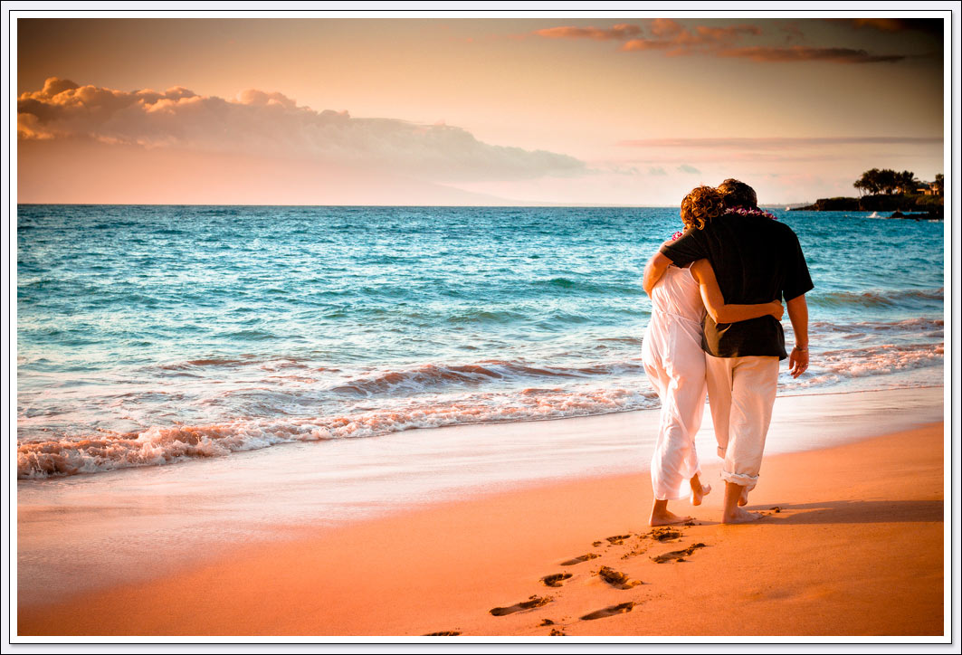 Maui sunset with newlyweds walking along the beach leaving their footprints behind them - Maui Hawaii