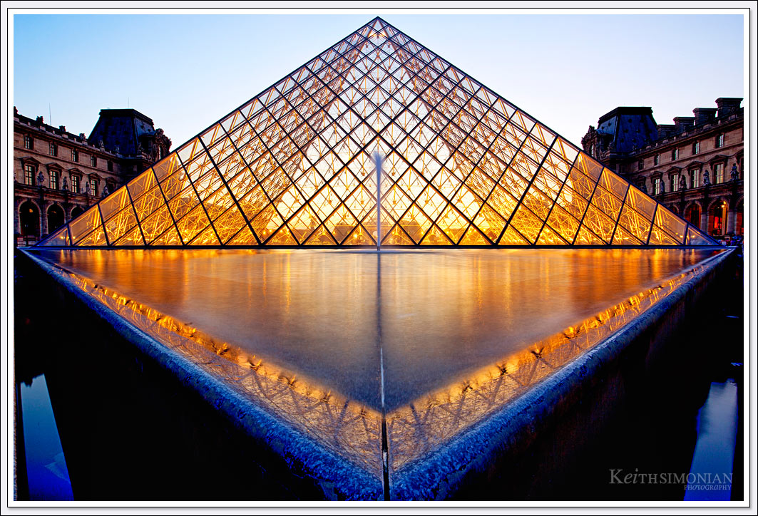 The reflection pond and the glass pyramid designed by I. M. Pei lit up during twilight at the Louvre Museum in Paris France.
