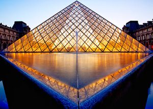 The glass pyramid designed by I. M. Pei lit up during twilight at the Louvre Museum in Paris France.