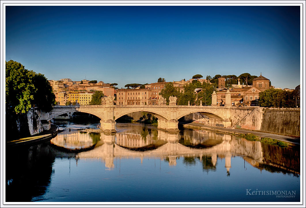 The low angle of the early morning sunlight allows the reflection of the Ponte vittorio Emanuele II bridge on the blue water of the Tiber River in Rome.