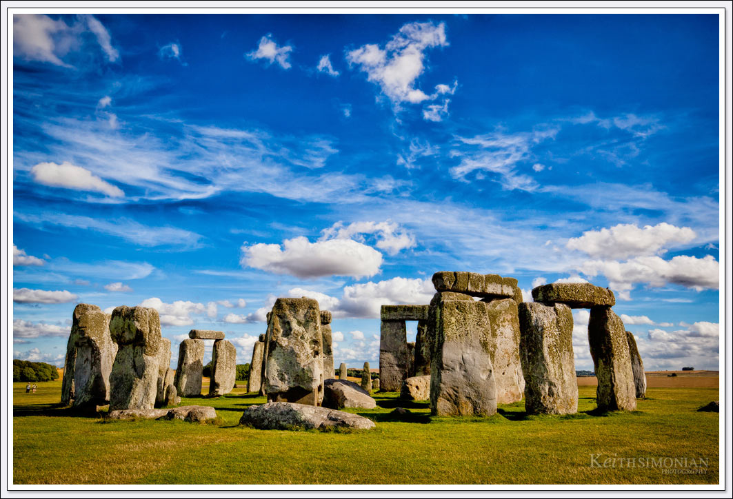 The rare sunny day with blue skies and nice white clouds over the famous prehistoric monument in Wiltshire, England that is Stonehenge.