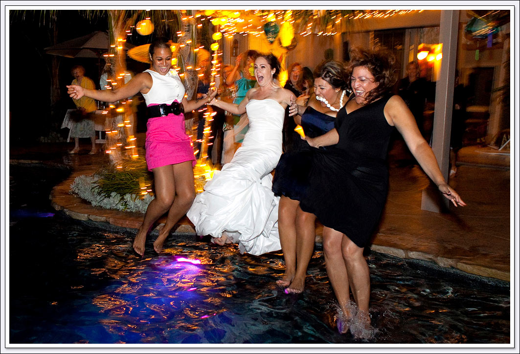 Bride and bridesmaids trashing their dresses by jumping into the swimming pool at this backyard wedding reception.