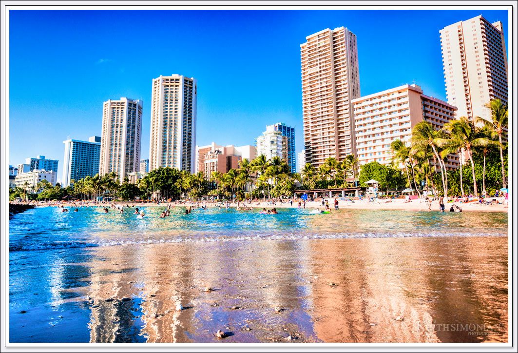 Some of the many hotels along Waikiki Beach reflect in the calm beach water