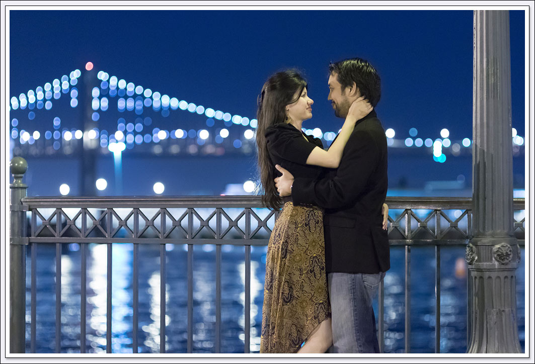 The lights of the Oakland - San Francisco Bay Bridge serve as a backdrop for nighttime engagement photos